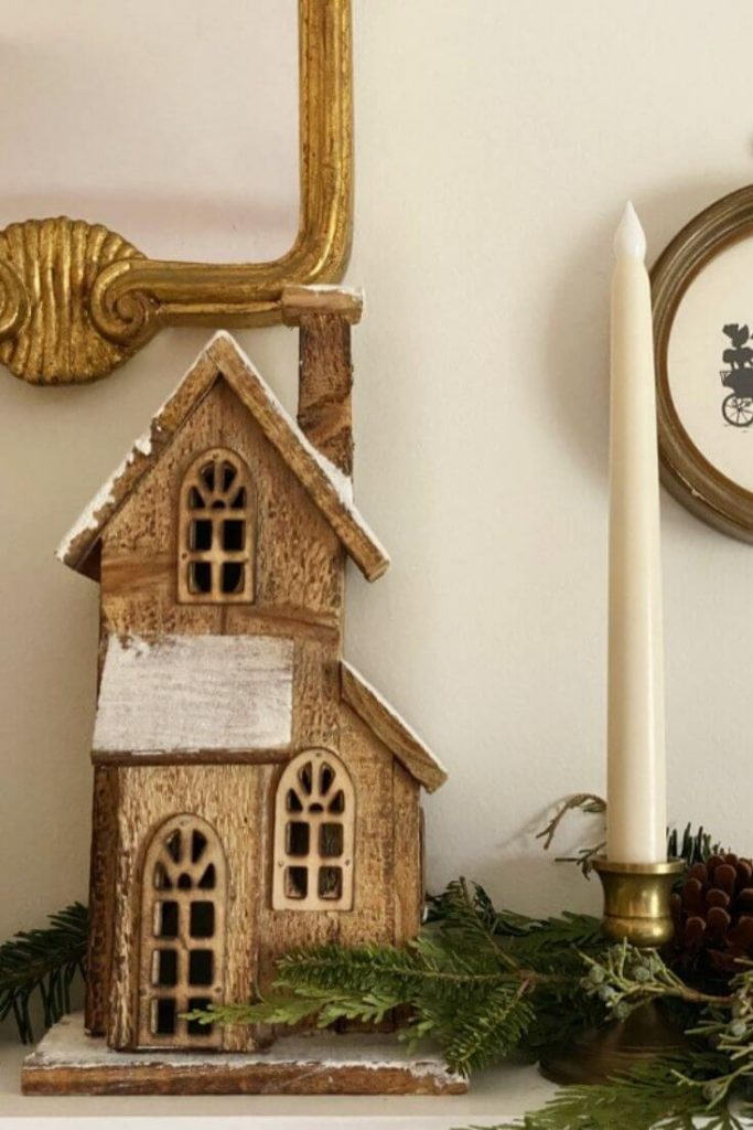 Christmas house on shelf with greenery and a candlestick
