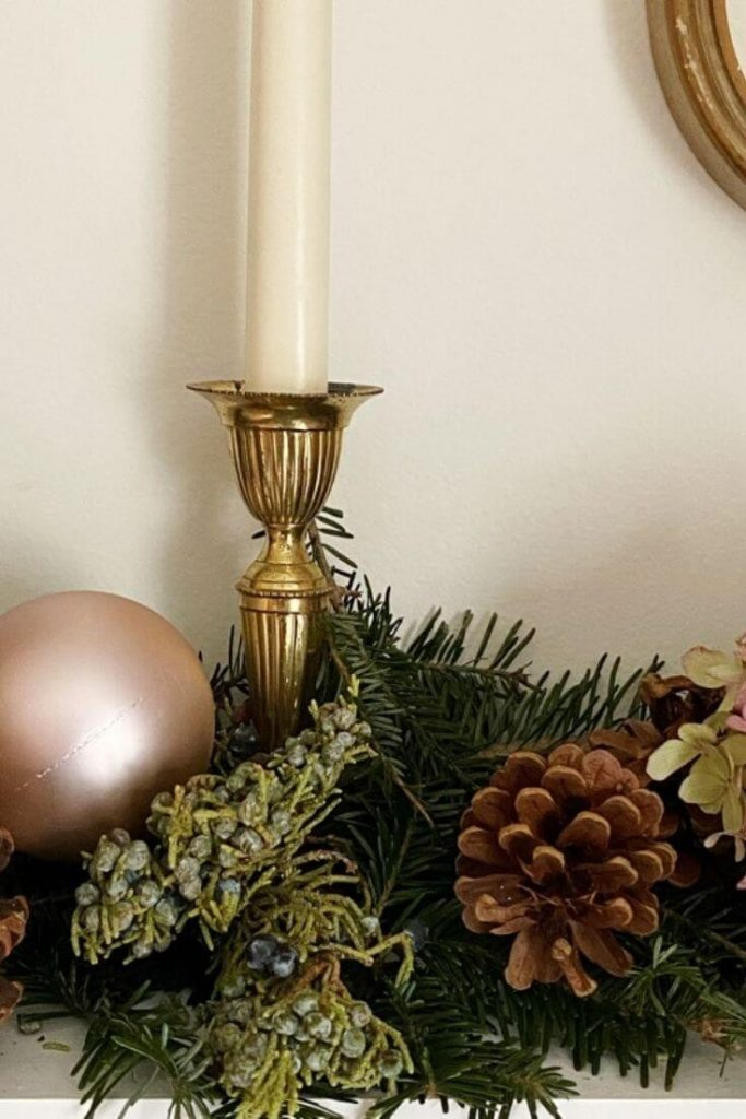 Brass candlestick mixed with greenery pinecones and blush pink Christmas bulb
