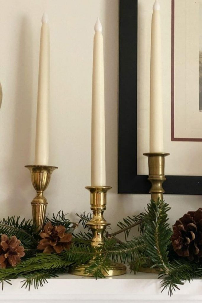 Three brass candlesticks arranged on a shelf with greenery and pinecones