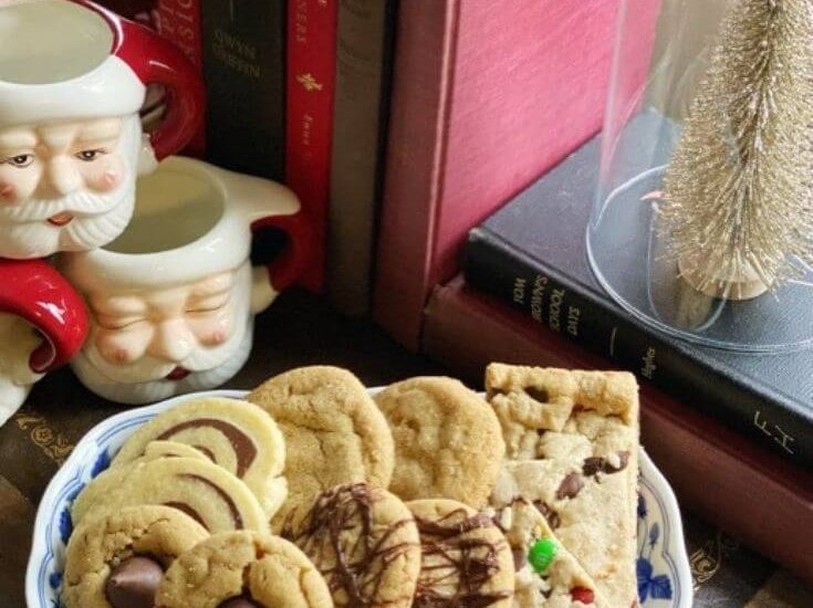 Plate of Christmas cookies on a top a wooden dresser next to Santa mugs and books