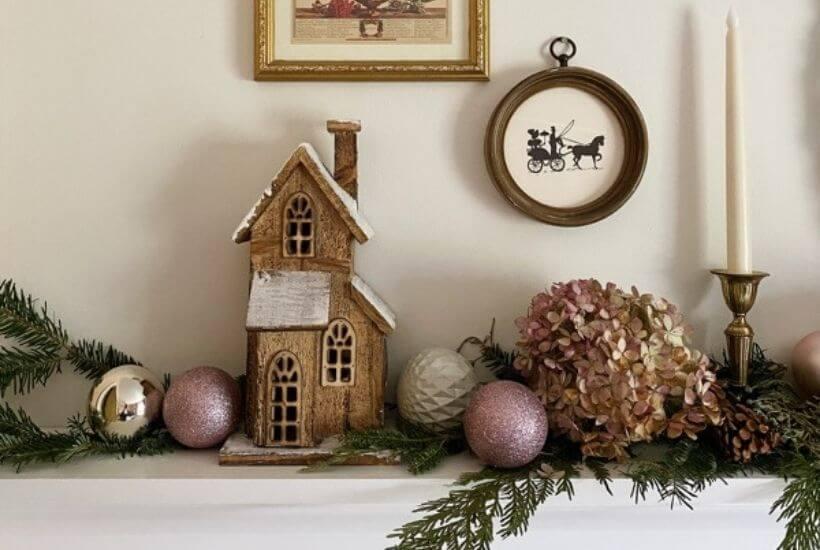 Feminine Christmas shelf display with dried hydrangea fresh greenery Christmas bulbs and wooden house