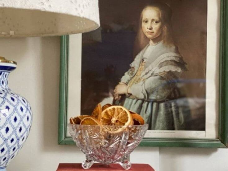 Dish of dried oranges atop a stack of books on a nightstand