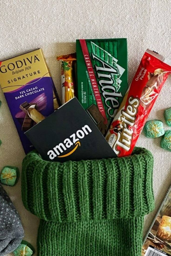 Assortment of candy and a gift card coming out of the top of a stocking