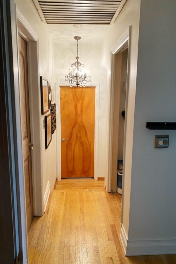 View of short upstairs hallway with a linen closet at the top of the stairs on the right and a bathroom door on the left. Closed bedroom door straight ahead.