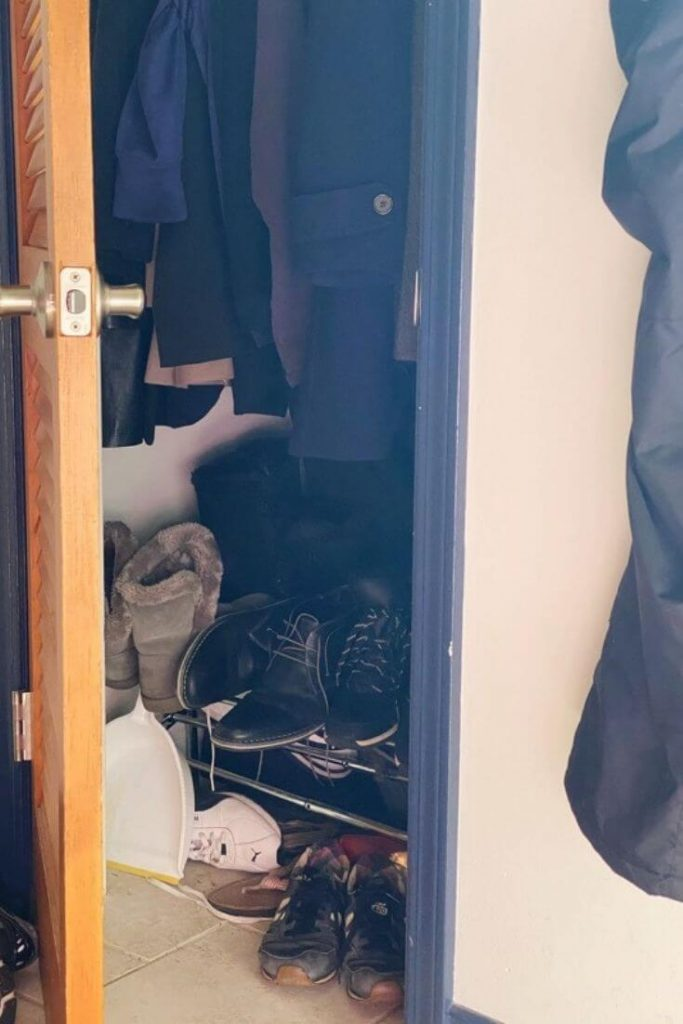 Interior shot of a messy entryway closet with coats hanging above a bunch of shoes below