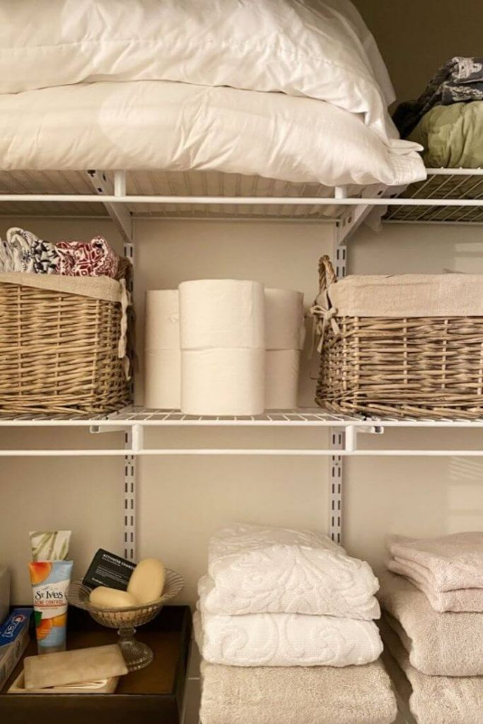 Inside of a linen closet with folded towels extra toiletries and pillows