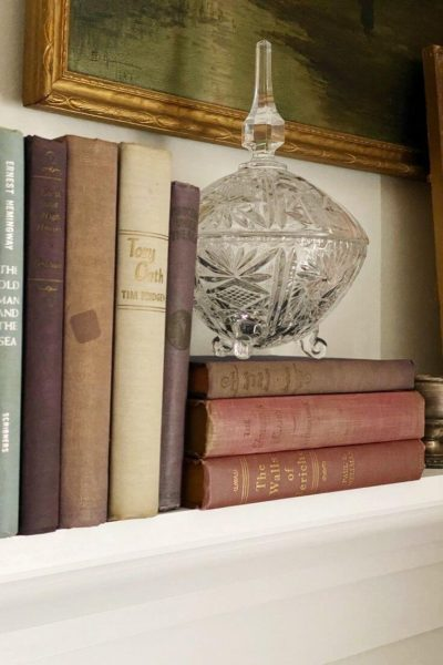 A glass candy dish atop a stack of books on a shelf