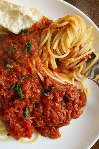 Plate of spaghetti with a hearty and thick Italian Sunday gravy sauce