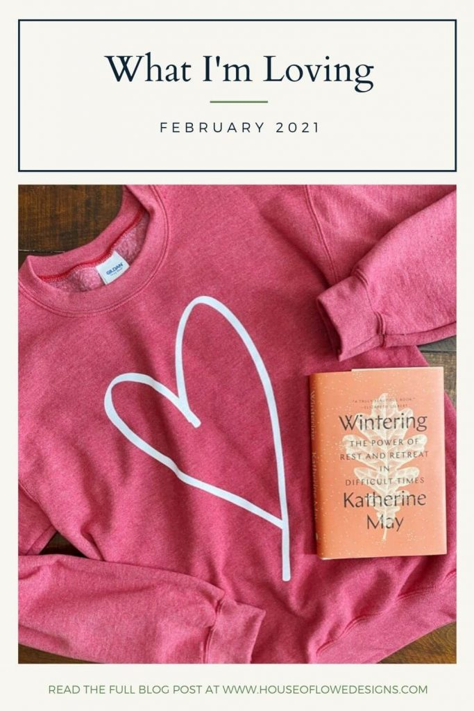 Heathered red sweatshirt with white heart for Valentine's Day and the book Wintering by Katherine May on top