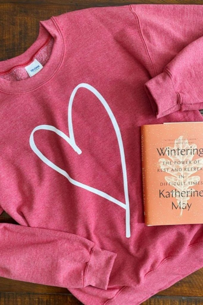 Heathered red sweatshirt with white heart for Valentine's Day with Wintering book by Katherine May on top
