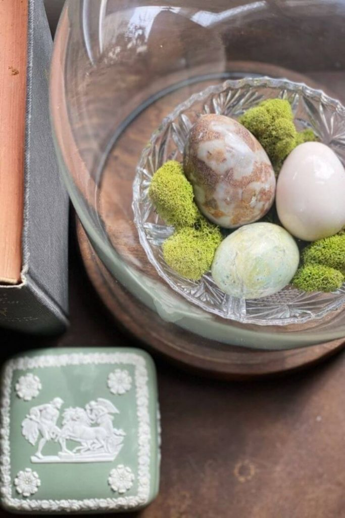 Marble eggs and moss in a glass dish under a cloche are perfect spring decor for your home