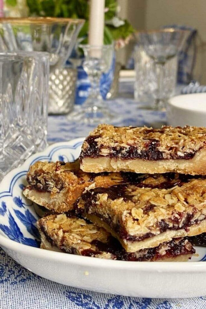 A stack of blackberry streusel bars on a blue and white dish