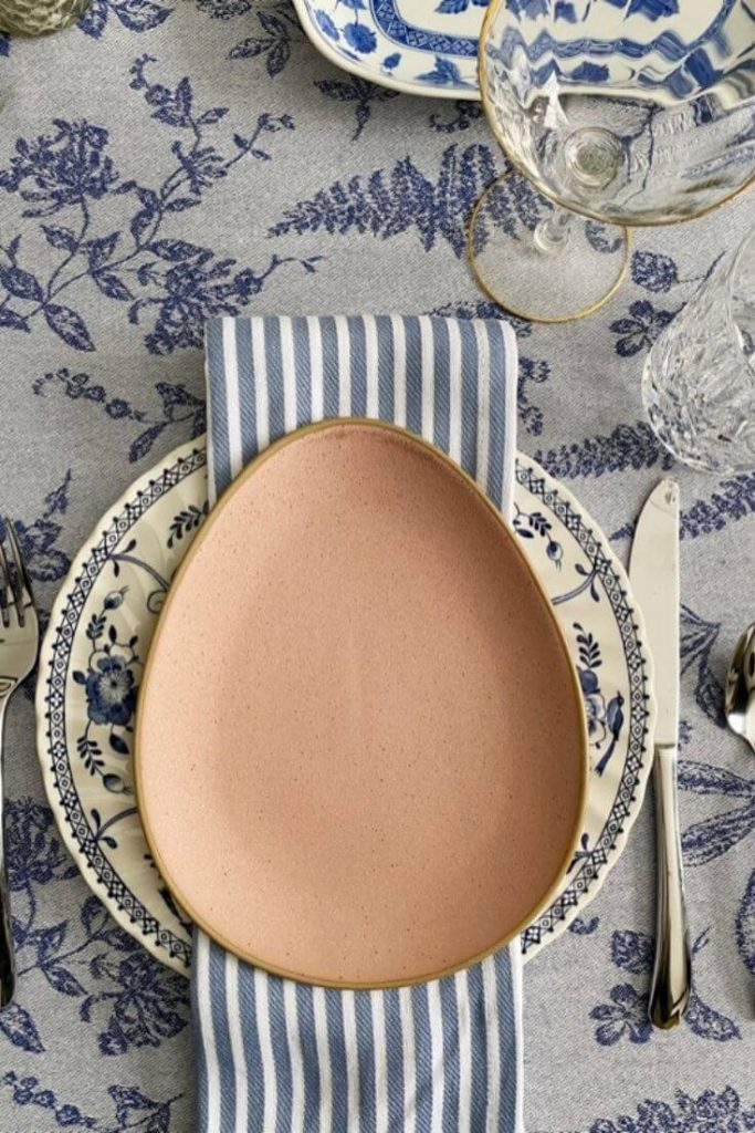 An Easter place setting with blue and white plates mixed with pink egg-shaped stoneware plates and striped blue and white napkins