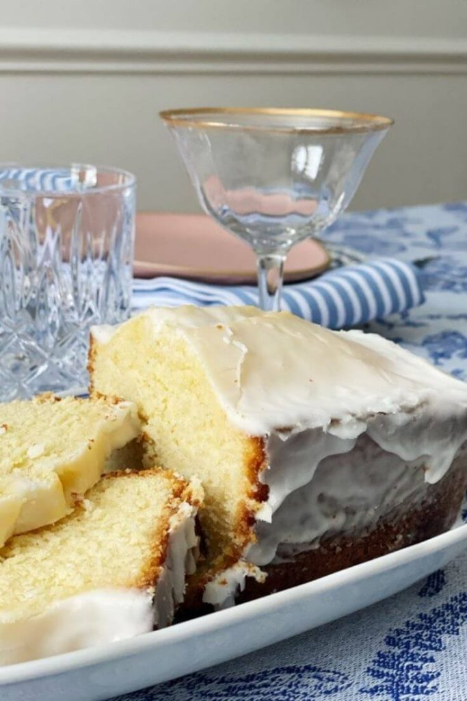 Iced lemon pound cake in a dish on a table set for Easter