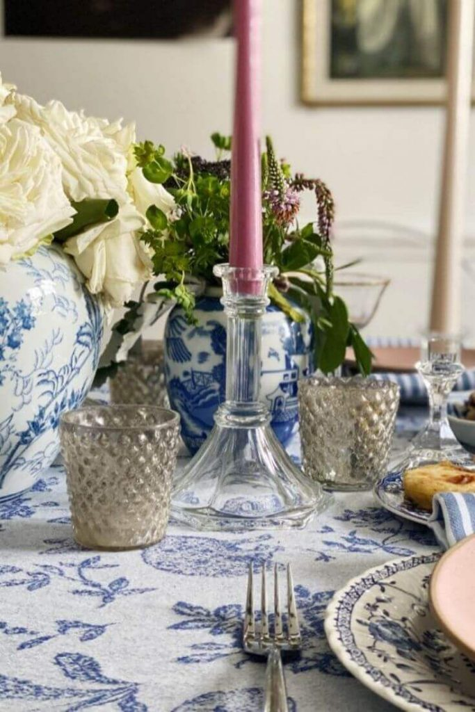 Clear glass candlesticks mixed with blue and white pottery pieces make for a beautiful and spring like Easter tablescape