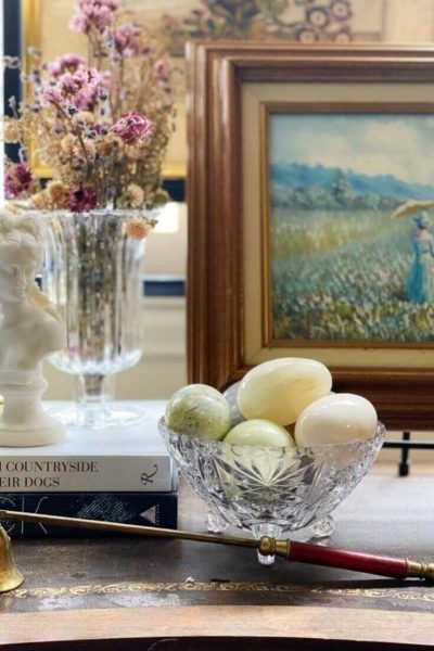 A stack of books with a female bust and glass vase with dried flowers arranged on a console with a small painting and glass dish with marble eggs for spring