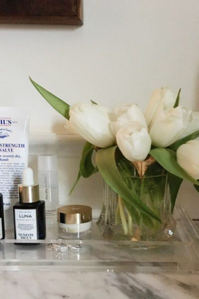A clear acrylic tray corrals a white tulip bouquet and skin care products atop a bathroom vanity