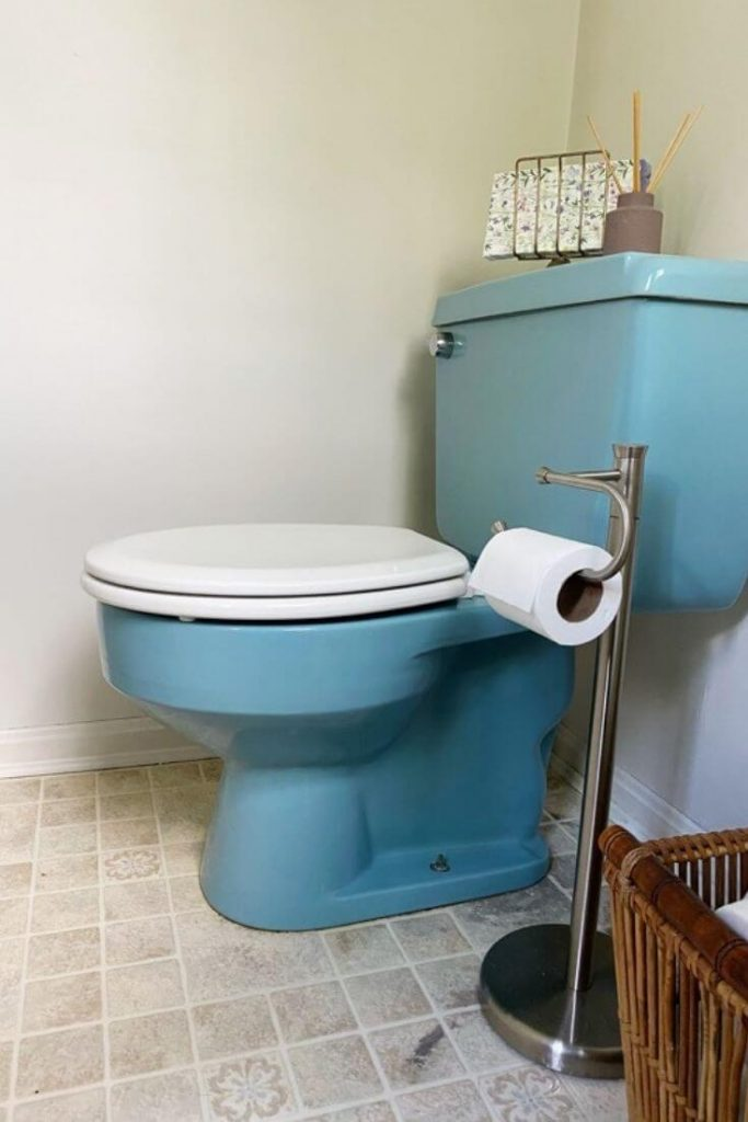 Blue toilet with white toilet seat in a half bathroom