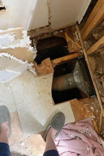 Half bath renovation demo showing hole in bathroom floor