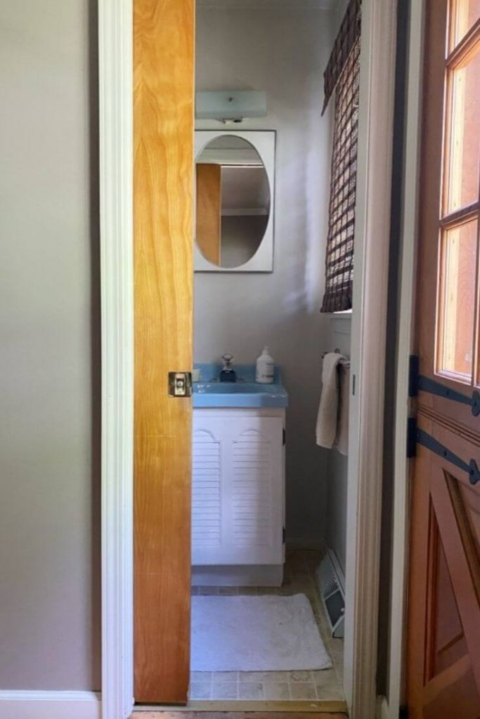 View past a pocket door into a small dated half bathroom