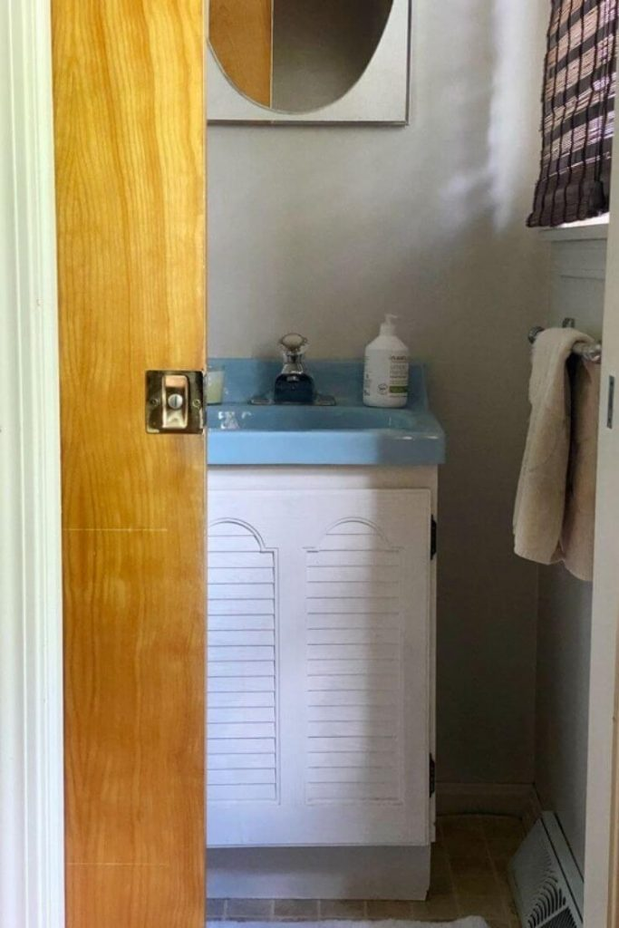 View past a pocket door into a small half bathroom where a dated white vanity sits with a blue sink