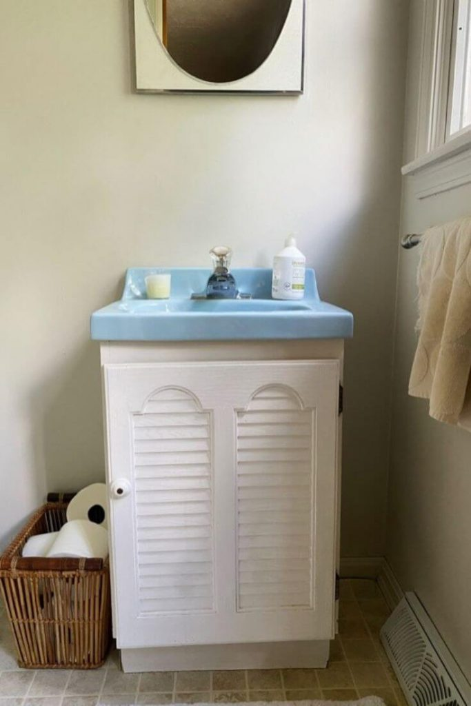 Dated white vanity with blue sink in small white bathroom