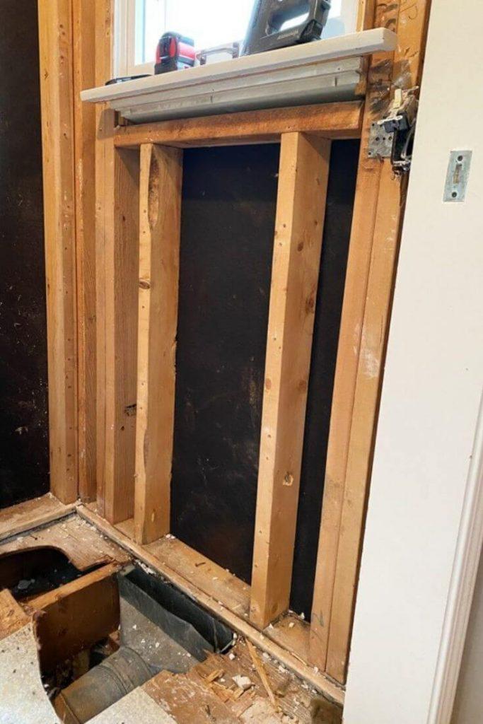open wall showing studs below bathroom window