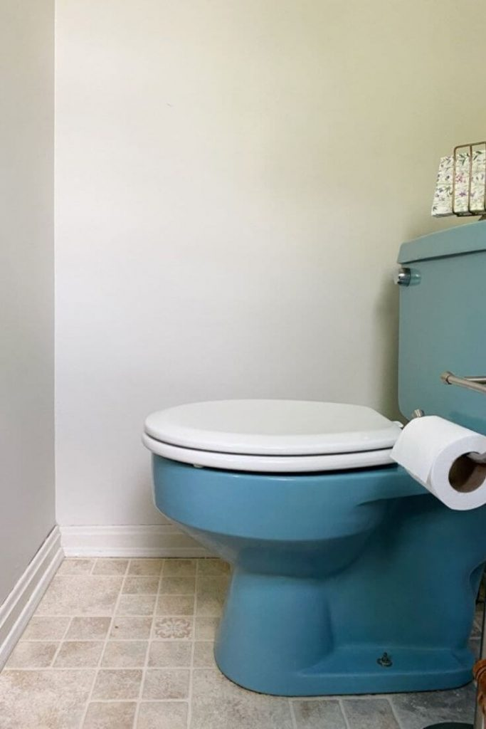 Blue toilet with a white toilet seat in a small half bath
