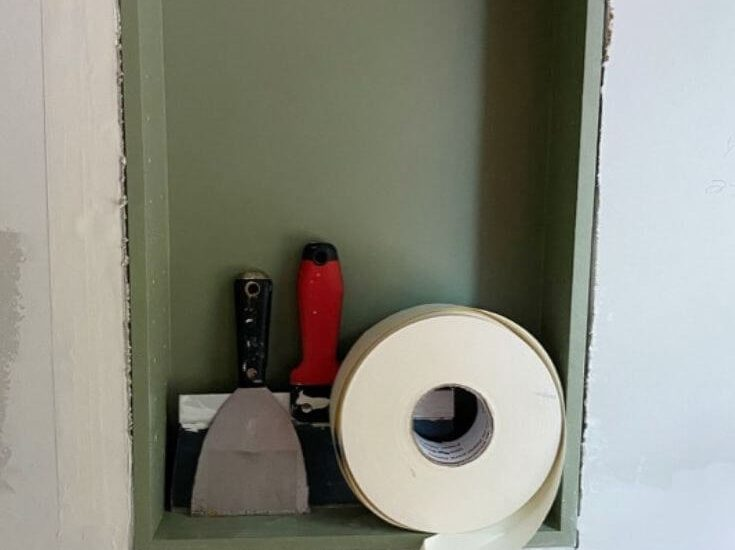 Drywall knives and tape in a bathroom niche