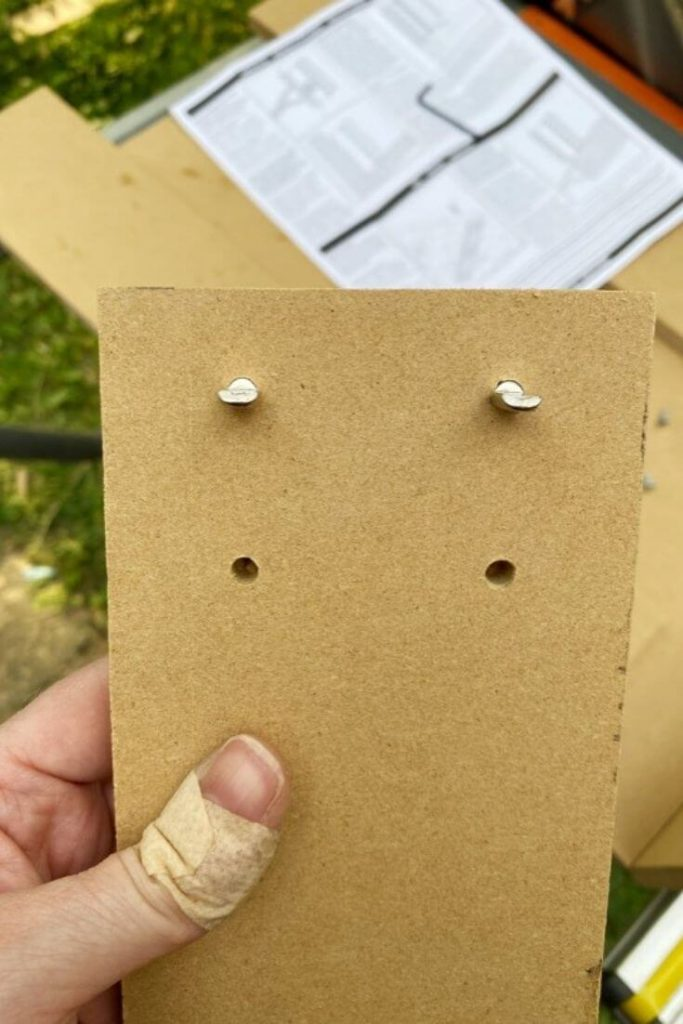 Holes created by the Kreg tool for shelf pins in a piece of MDF board