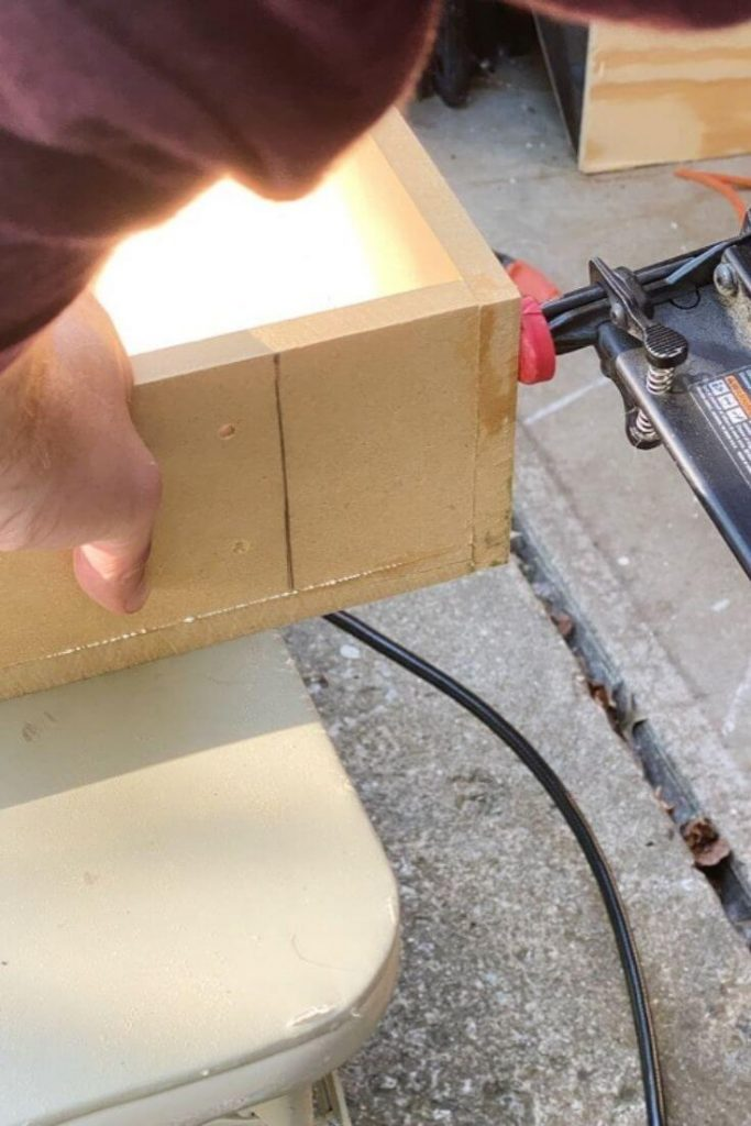 Using a nail gun to secure a corner of the MDF cabinet