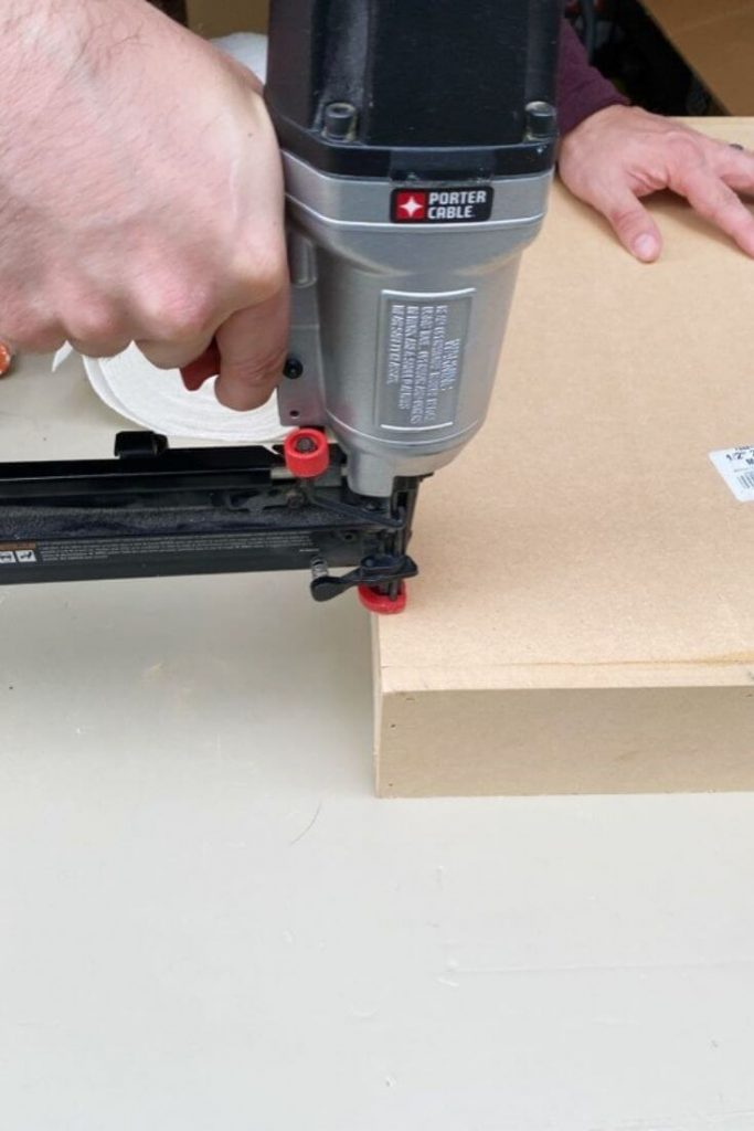 Using a nail gun to secure the back of the MDF medicine cabinet
